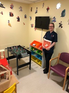 Sarah Whibley with the new books in the children's waiting room
