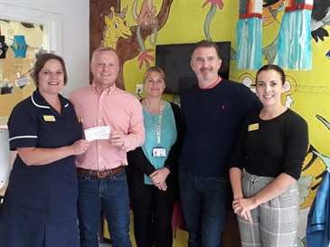 Mr Leitch and main sponsor Jess Roullier presenting the cheque to staff on Rainbow Ward