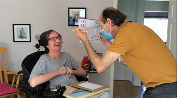 Tony Wright, in a wheelchair, with carer Richard Wood. Richard is holding the Eye Talk device and using it to help Tony communicate