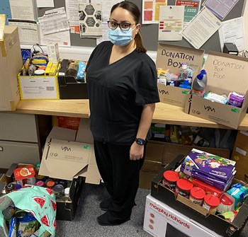 Elmas Deniz with some of the items that have been donated for the foodbank. She is in an office with boxes on the desk and floor full of donated items.