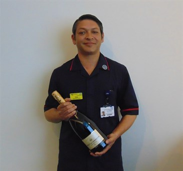 Avatar of Chris Hamson, who has recieved a Chief Nursing Officer's Silver Award. He is pictured in uniform holding a bottle of Champagne