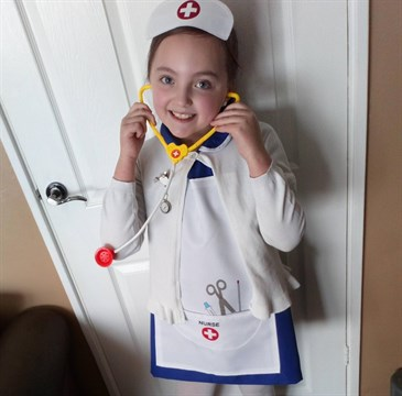 Reegan Price, who dressed as a nurse for superheroes day at school after NHS staff saved her dad's life. She is pictured wearing a nurse's uniform including hat, and holding a stethoscope, in front of a white door in her living room